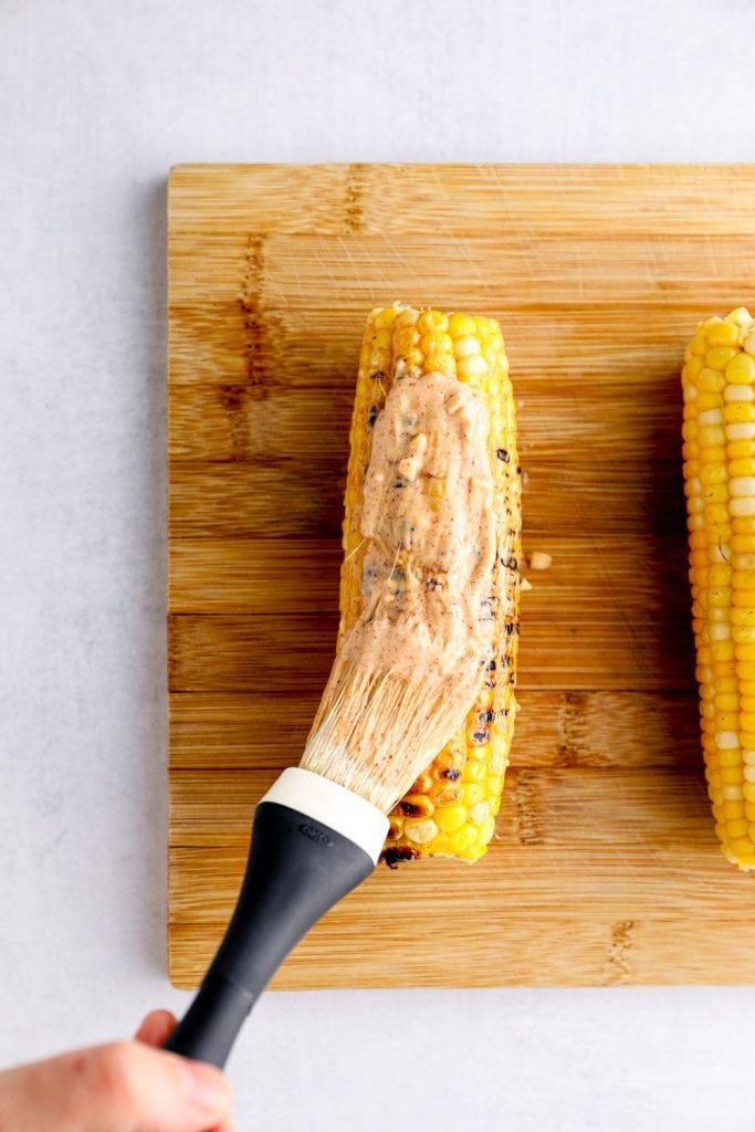Grilled corn being brushed with chili mayo.