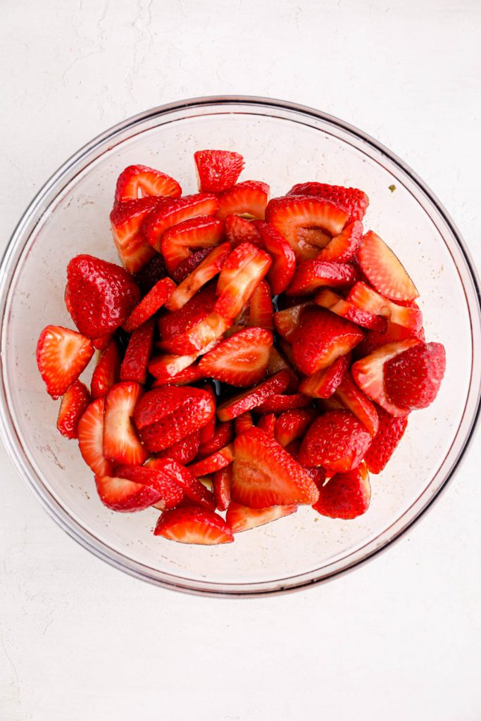 Sliced strawberries in a bowl tossed with balsamic vinegar.
