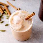 An iced chai latte with a cinnamon stick garnish.