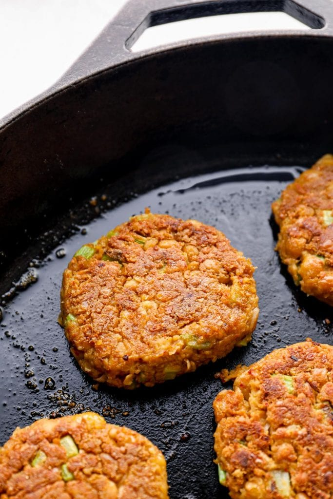 Chickpea patties being cooked in a cast iron skillet.