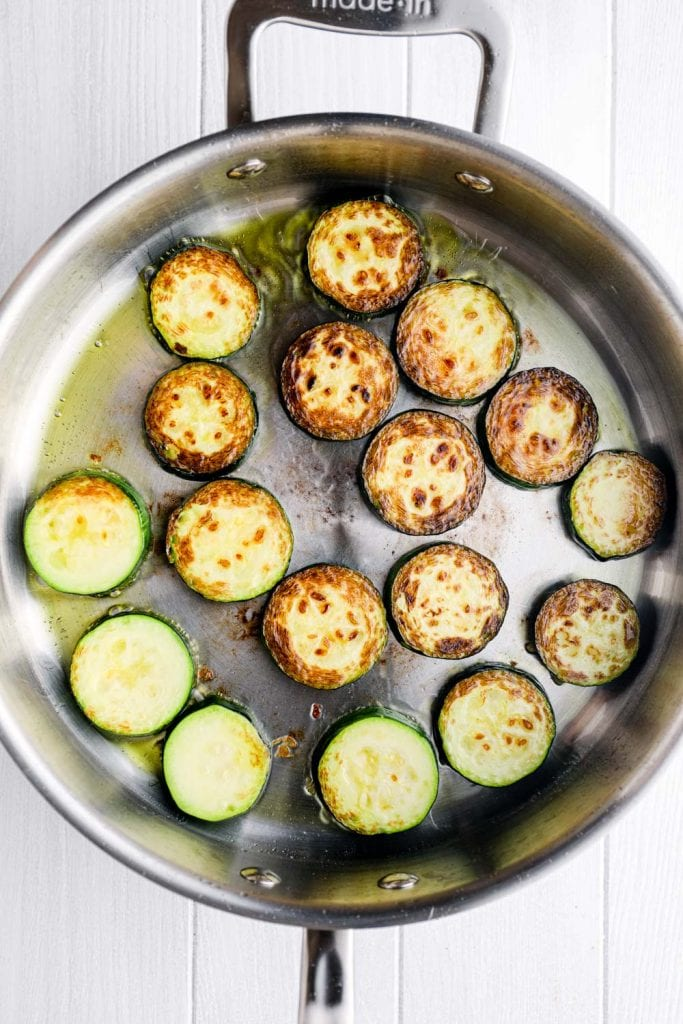 Seared zucchini and olive oil in a sauté pan.
