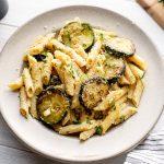 Pasta con zucchini on a beige plate.