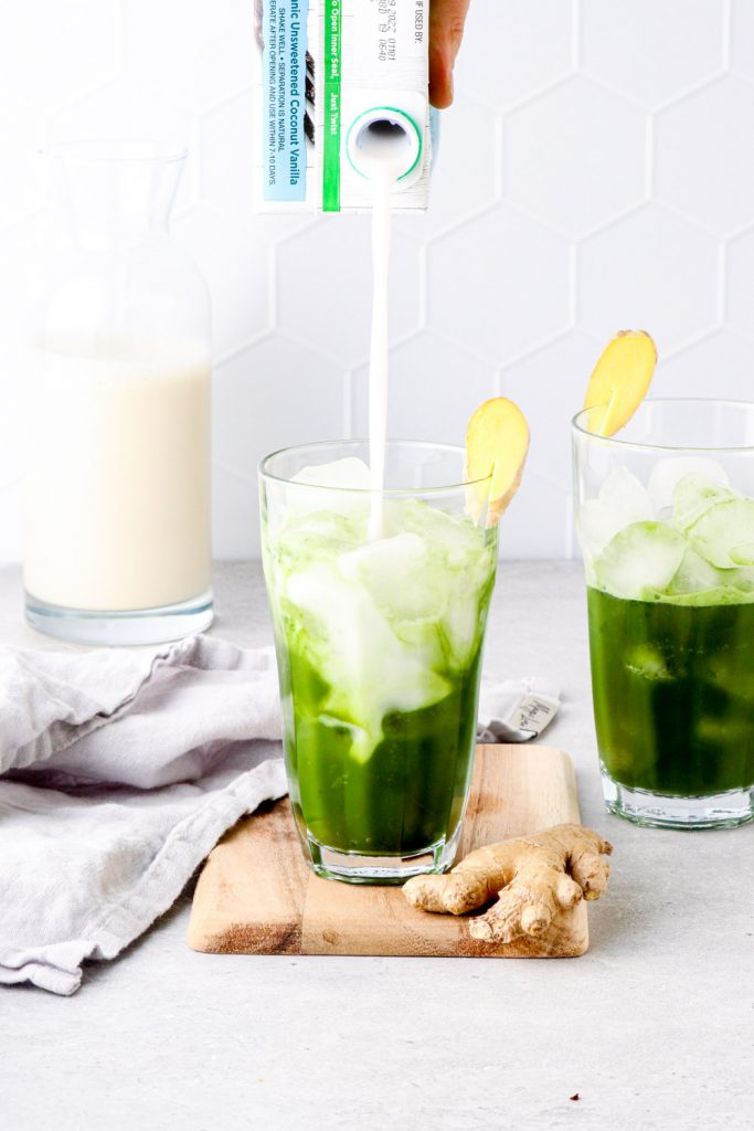 Coconut milk pouring into a pineapple matcha drink.