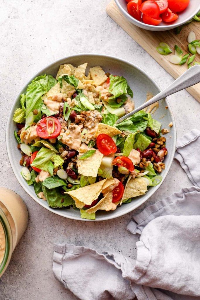 Vegan taco salad tossed with dressing.