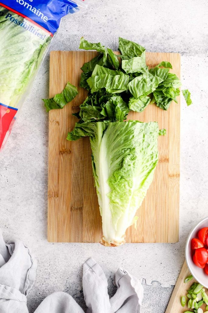 Romaine lettuce being chopped on a bamboo cutting board.