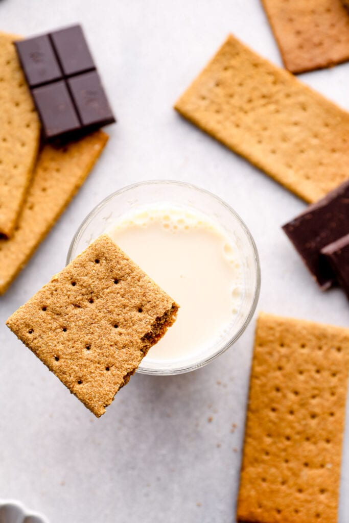 A gluten free graham cracker balanced on a glass of milk.