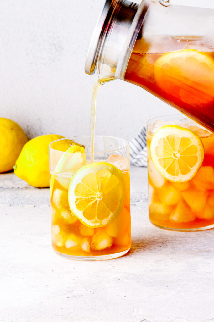 Iced tea pouring into a glass with lemon sliced.