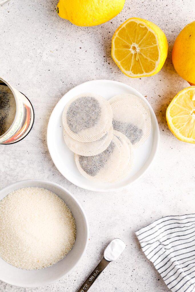 Ingredients to make lemon iced tea: lemons, tea bags, sugar, and baking soda.