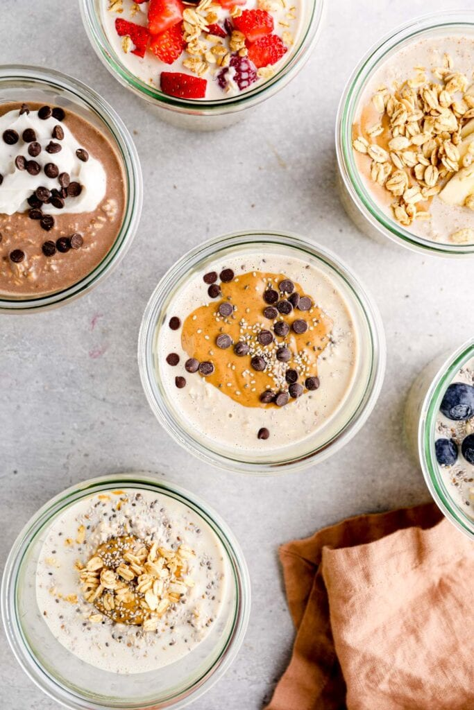 All the flavors of protein overnight oats in glass jars.