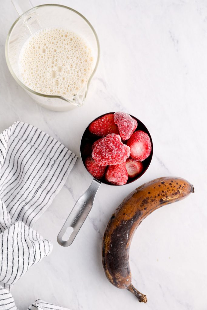 Milk, strawberries, and banana on a marble background.