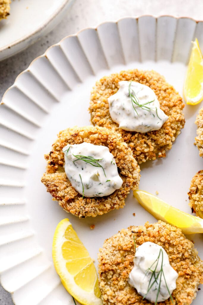 Vegan crab cakes with lemon wedges on a white plate.