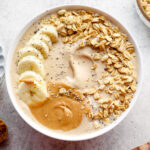 A banana smoothie in a white bowl with granola.