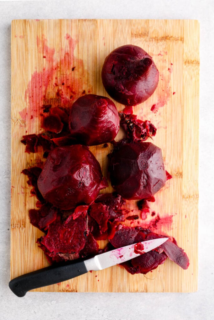 Peeled beets on a cutting board.