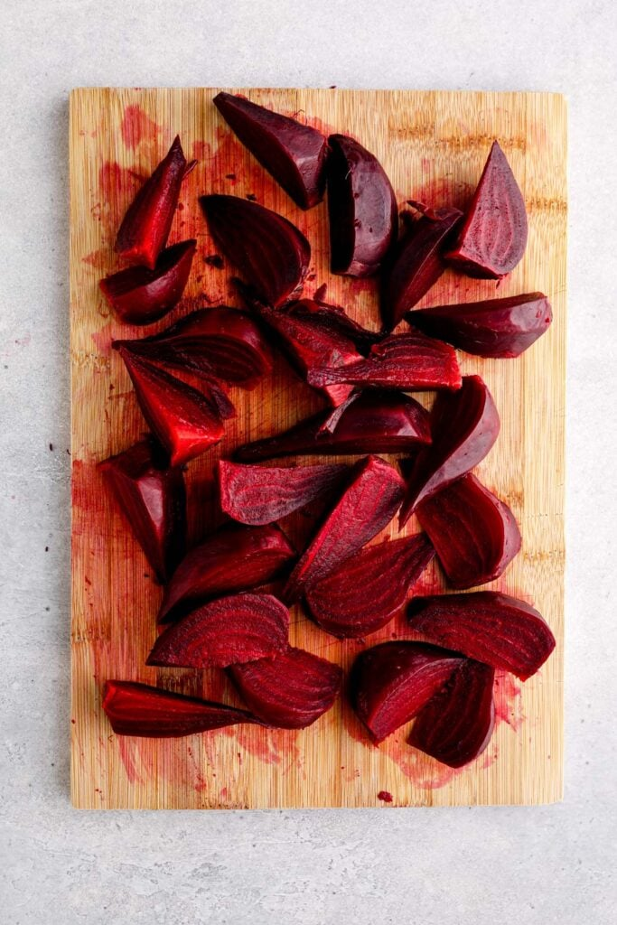 Beets cut into wedges on a cutting board.
