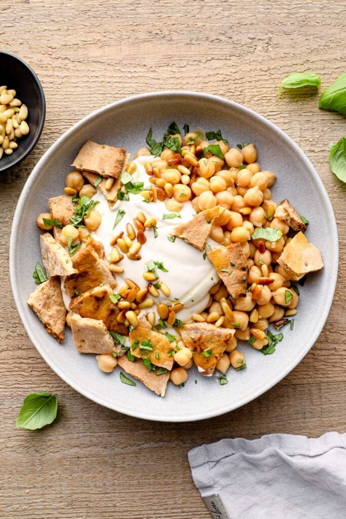 Fatteh salat with yogurt and toasted pita in a blue bowl.
