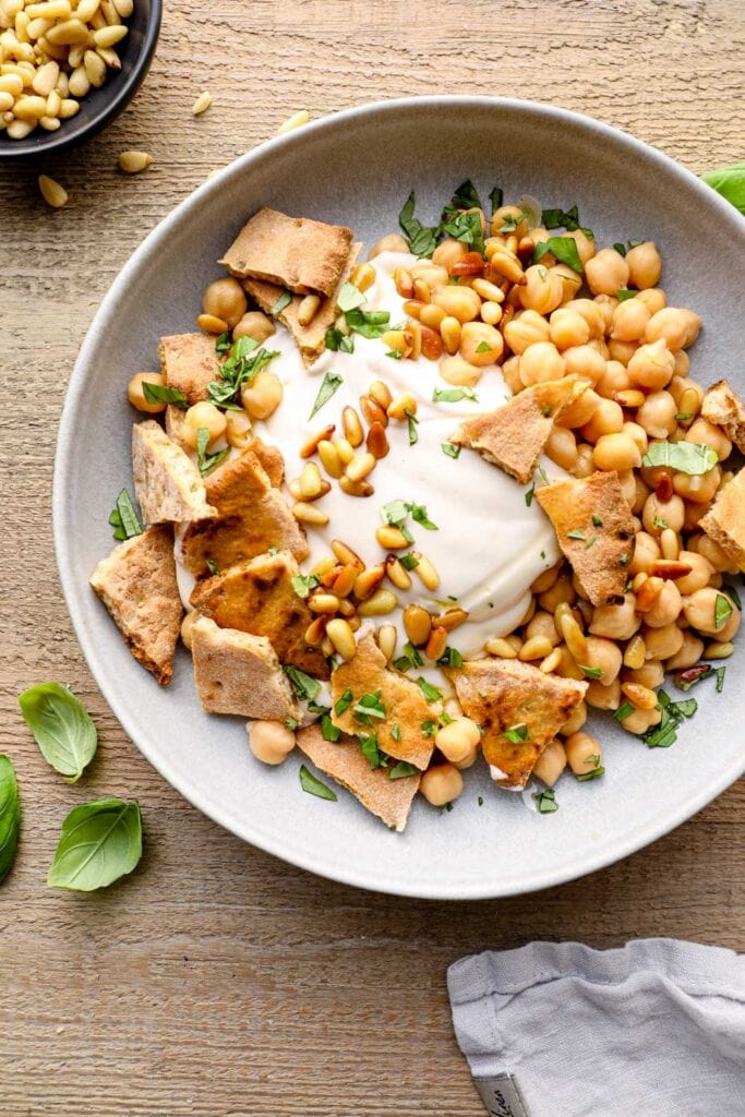 Pine nuts and parsley topping fatteh with chickpeas, pita bread and yogurt.