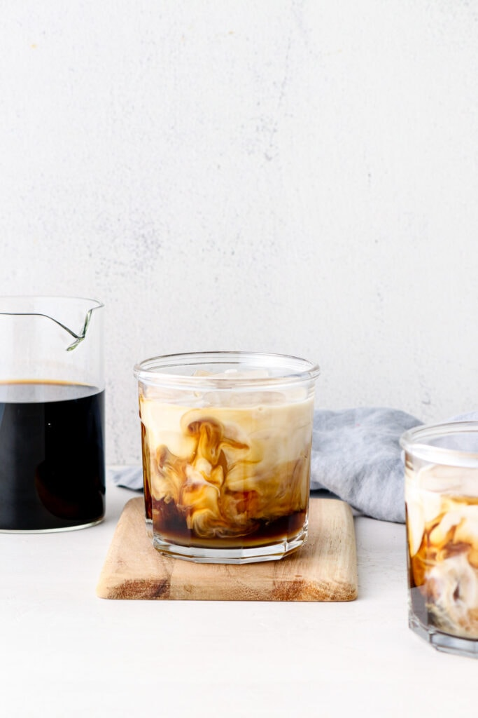 Almond milk swirling into cold brew with honey.