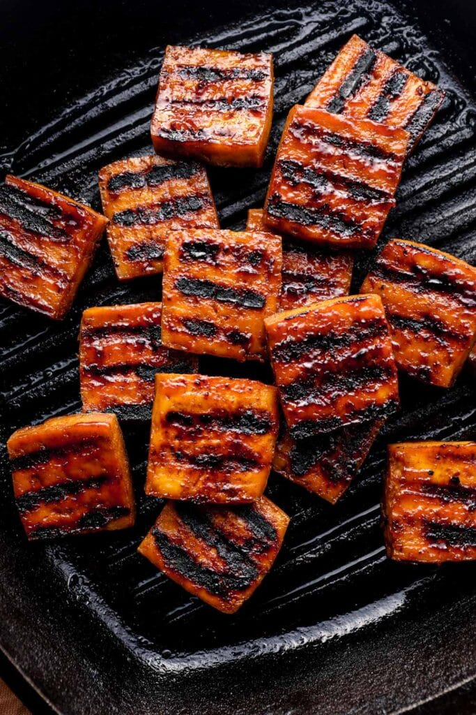 Smoked tofu stacked in a grill pan.