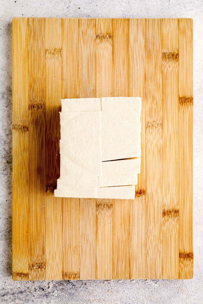 Tofu cut into squares on a bamboo cutting board..