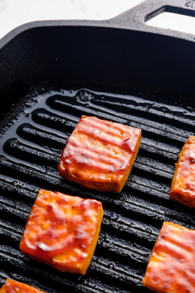Barbecue sauce brushed tofu on a grill pan.