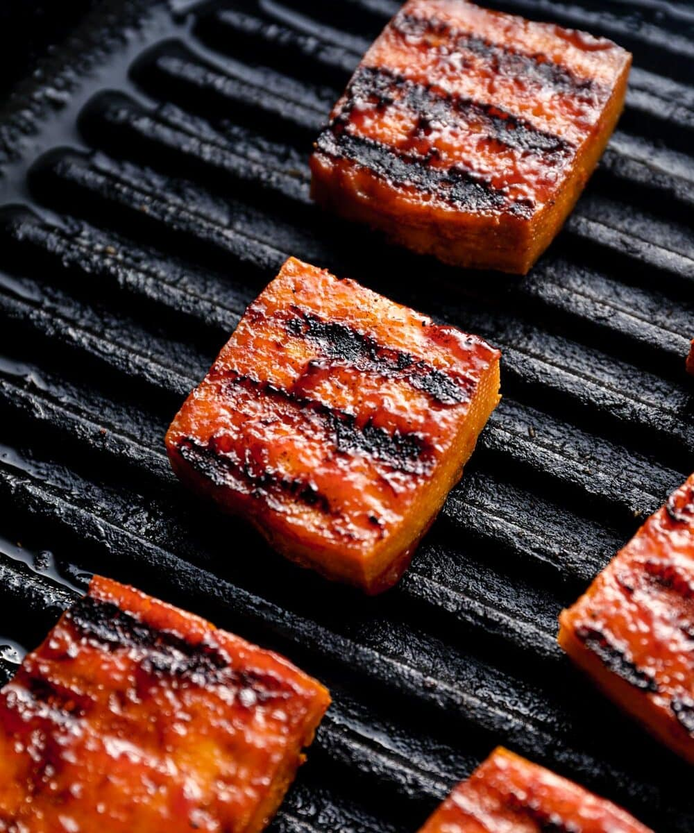 Smoked tofu with grill marks cooking in a grill pan.