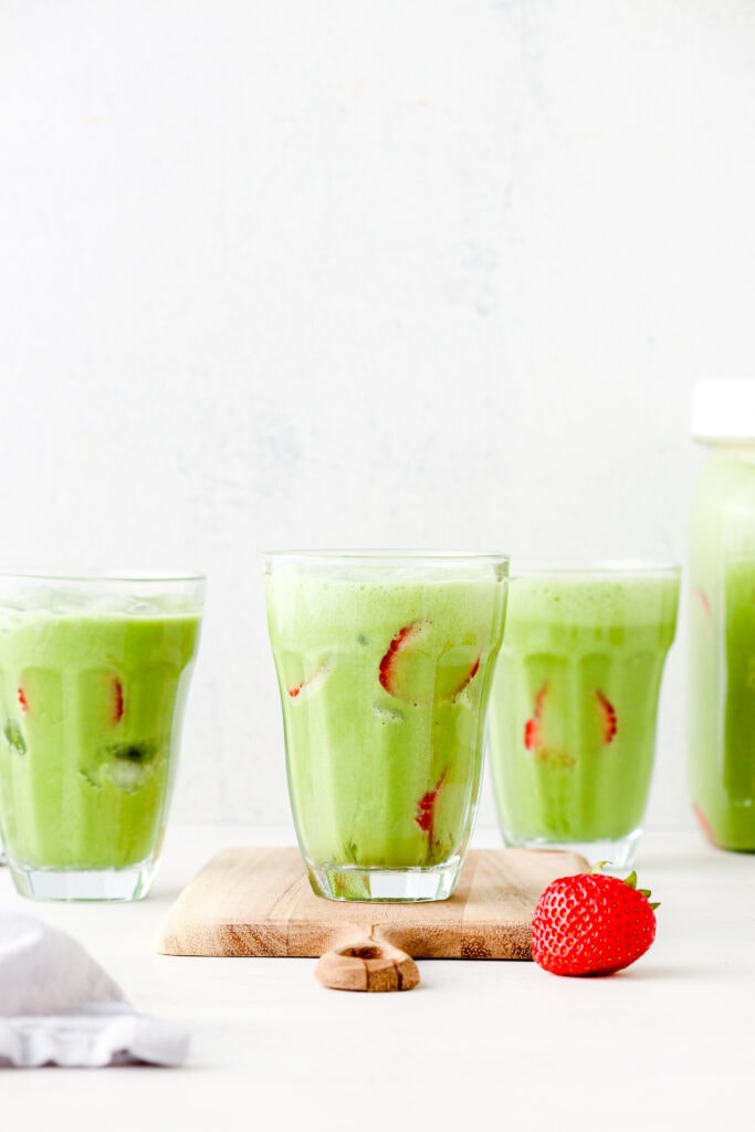 An iced matcha latte with sliced strawberries in a glass.