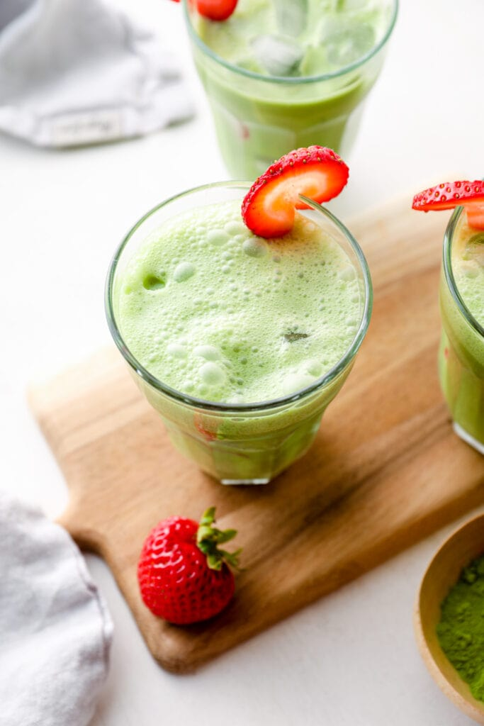 Three strawberry matcha lattes in glasses with ice.