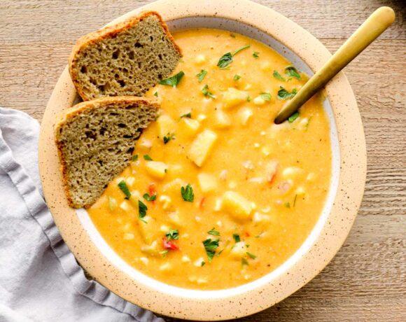 Bread dunking in vegan corn chowder.