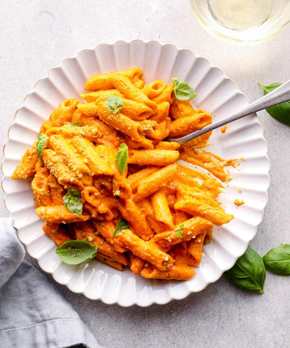 A plate of penne with vodka sauce and a glass of wine.