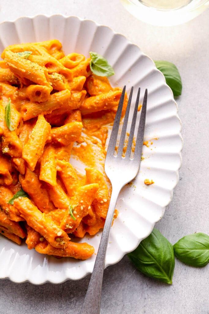 A bite of vegan vodka sauce pasta with basil.