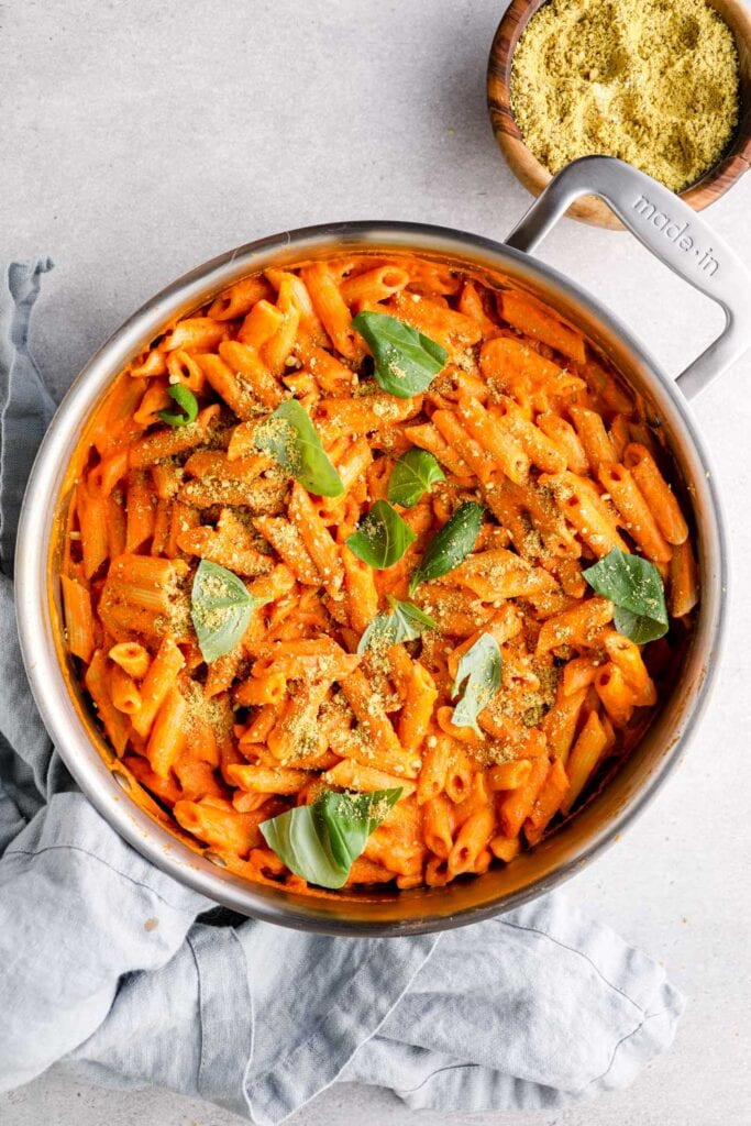 Vegan vodka sauce tossed with penne pasta in a skillet with parmesan and basil.