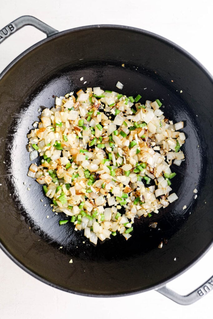 Onion, ginger, garlic, and jalapeno cooking in a pot.