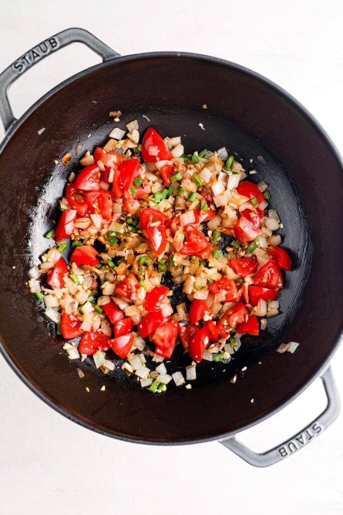 Tomatoes cooking with onion, jalapeno, and spices.