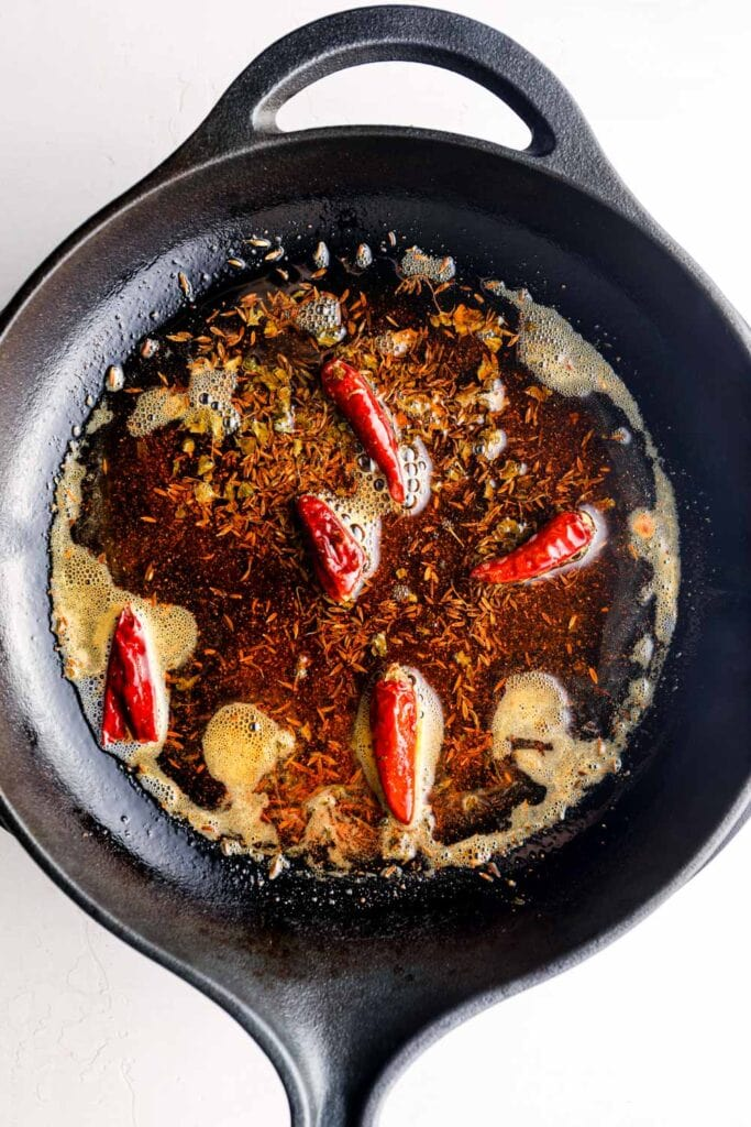 Tempering oil with cumin seeds and chilis in a cast iron skillet.