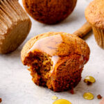 A bite out of a gluten free pumpkin muffin with honey and cinnamon.