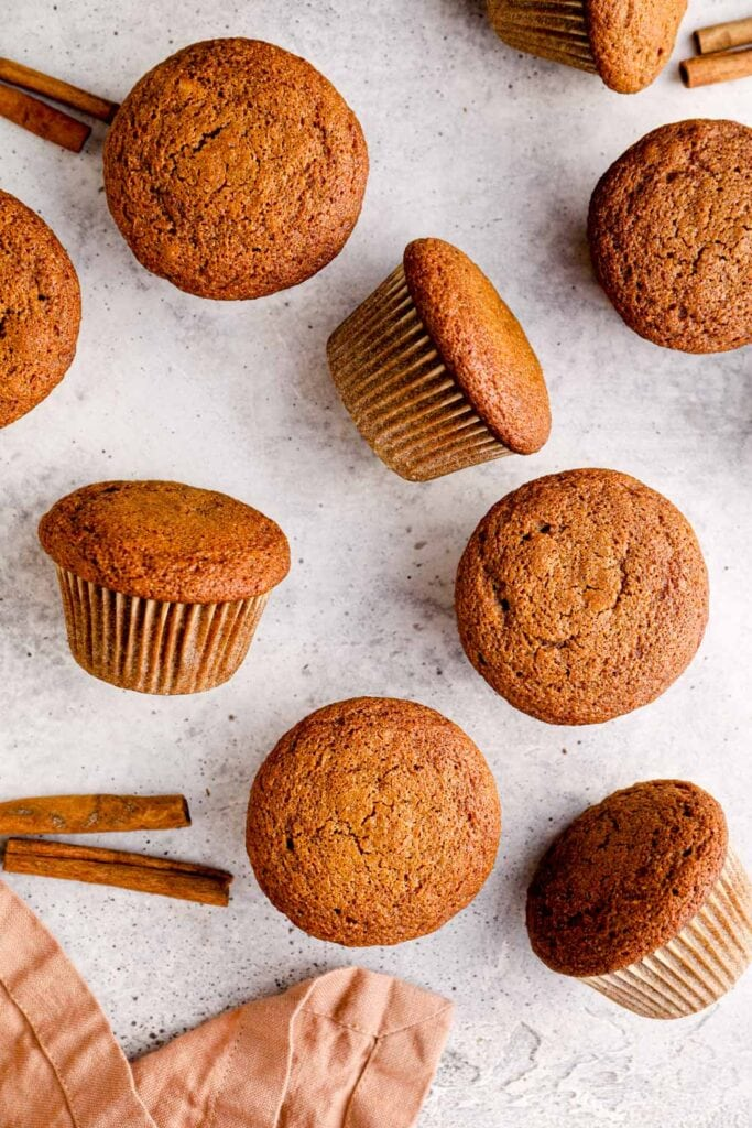 Gluten free pumpkin muffins on a grey background with a pink towel.