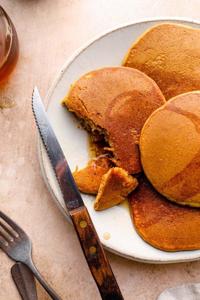 Cut gluten free pumpkin pancakes wit a knife.