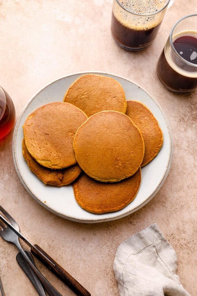 A plate of gluten free pumpkin pancakes with coffee.