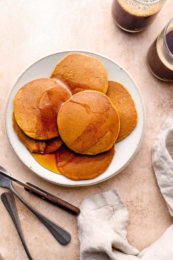Syrup drizzled onto gluten free pumpkin pancakes.