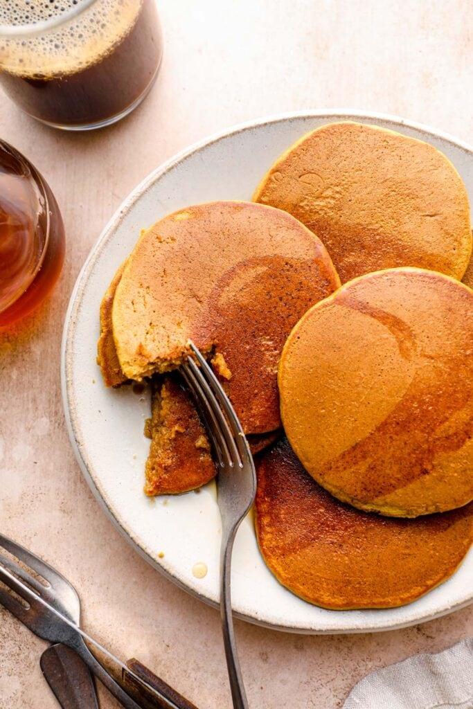 A bite out of a plate of gluten free pumpkin pancakes.