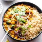 A bowl of chickpea and spinach curry with brown basmati rice.
