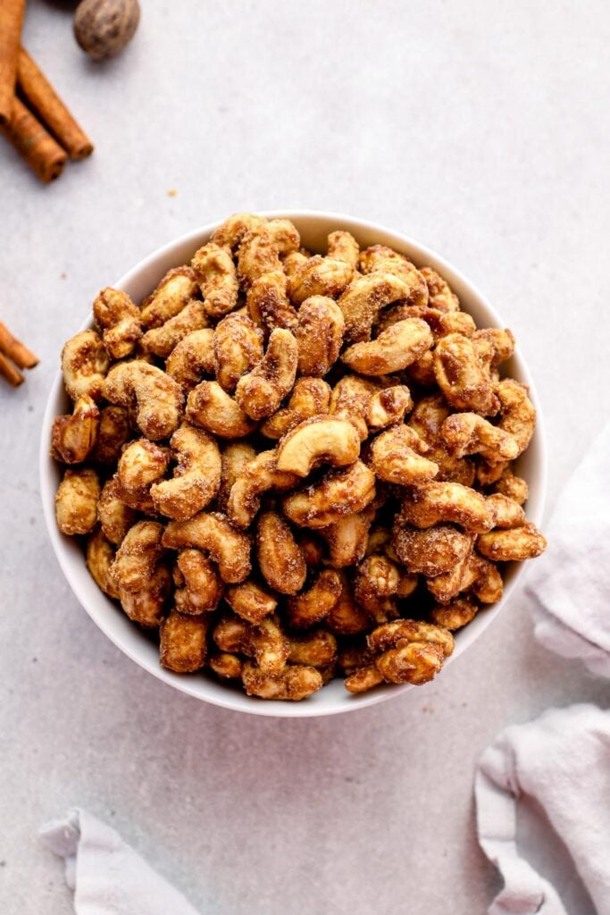 Spiced candied cashews in a bowl with cinnamon.