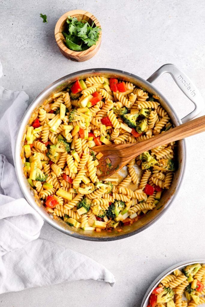 Red curry pasta in a stainless steel skillet.