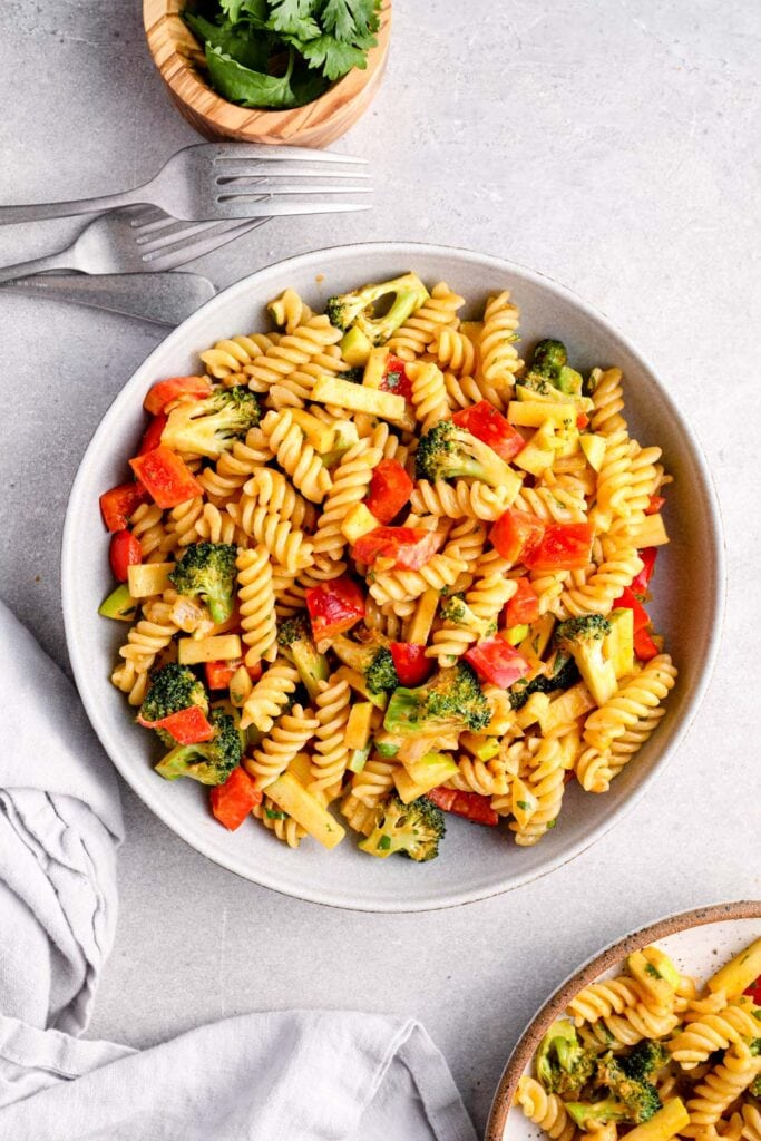 A bowl of red curry pasta with fusilli and broccoli.