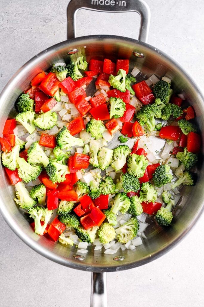Broccoli, bell pepper, onion, and garlic cooking in a sauté pan.